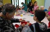 Infància i gent gran s'apropen en el taller intergeneracional de roses de Sant Jordi