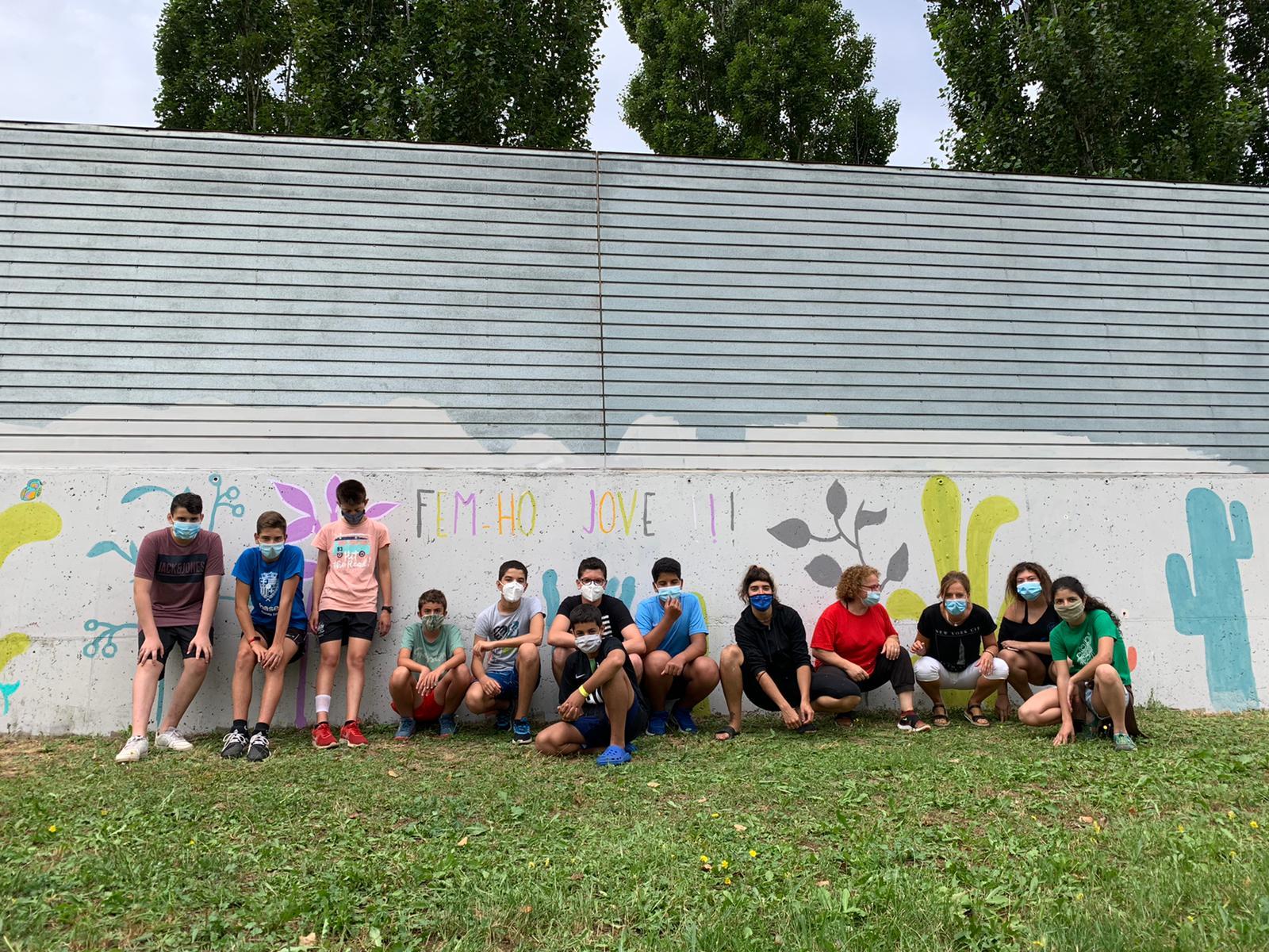 Joves de pintant pintant un mural a la paret del Pipican